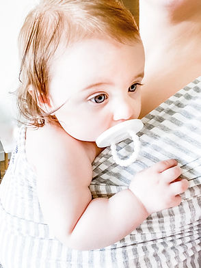 A super cute baby girl using one of our pacifiers (no longer available)