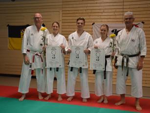Drei Mitglieder der Karateschule bestehen ihre Dan-Prüfung