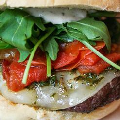 Hambúrguer Templário. Pão tradicional sem sementes, molho Santo Graal, hambúrguer de vaca, queijo provolone, molho chimichurri, confit de tomate com ervas aromáticas e rúcula.