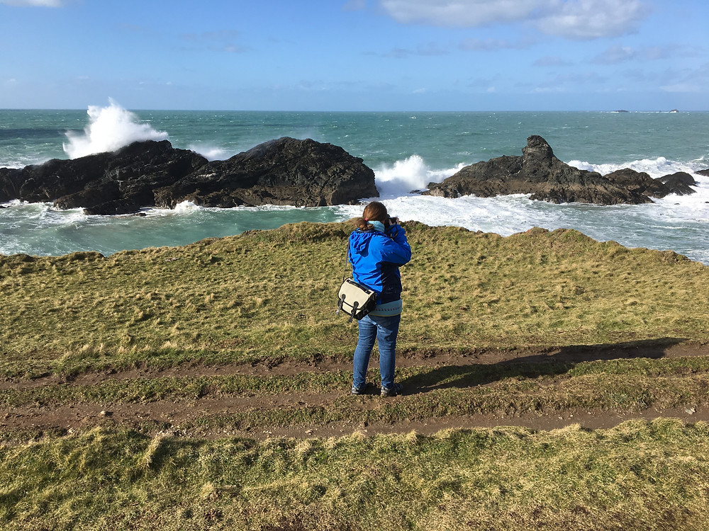 Lucinda Price holding camera up to seascape with wild waves and blue skies