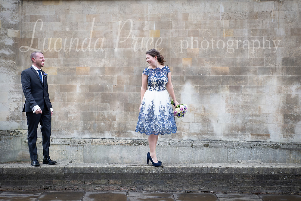 Couple looking towards each other standing on a low wall, woman holding bouquet of flowers in white and blue dress, man in suit Lucinda Price Photography wedding photographer