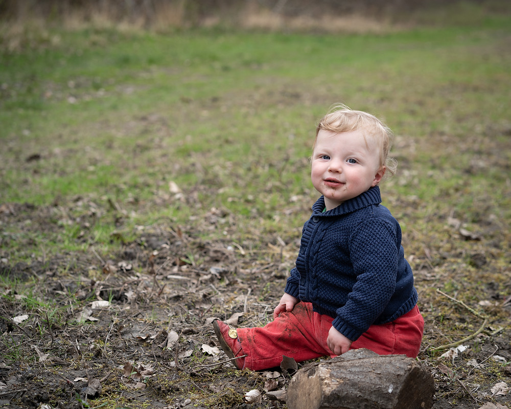 Young baby in mud sitting on ground smiling at camera