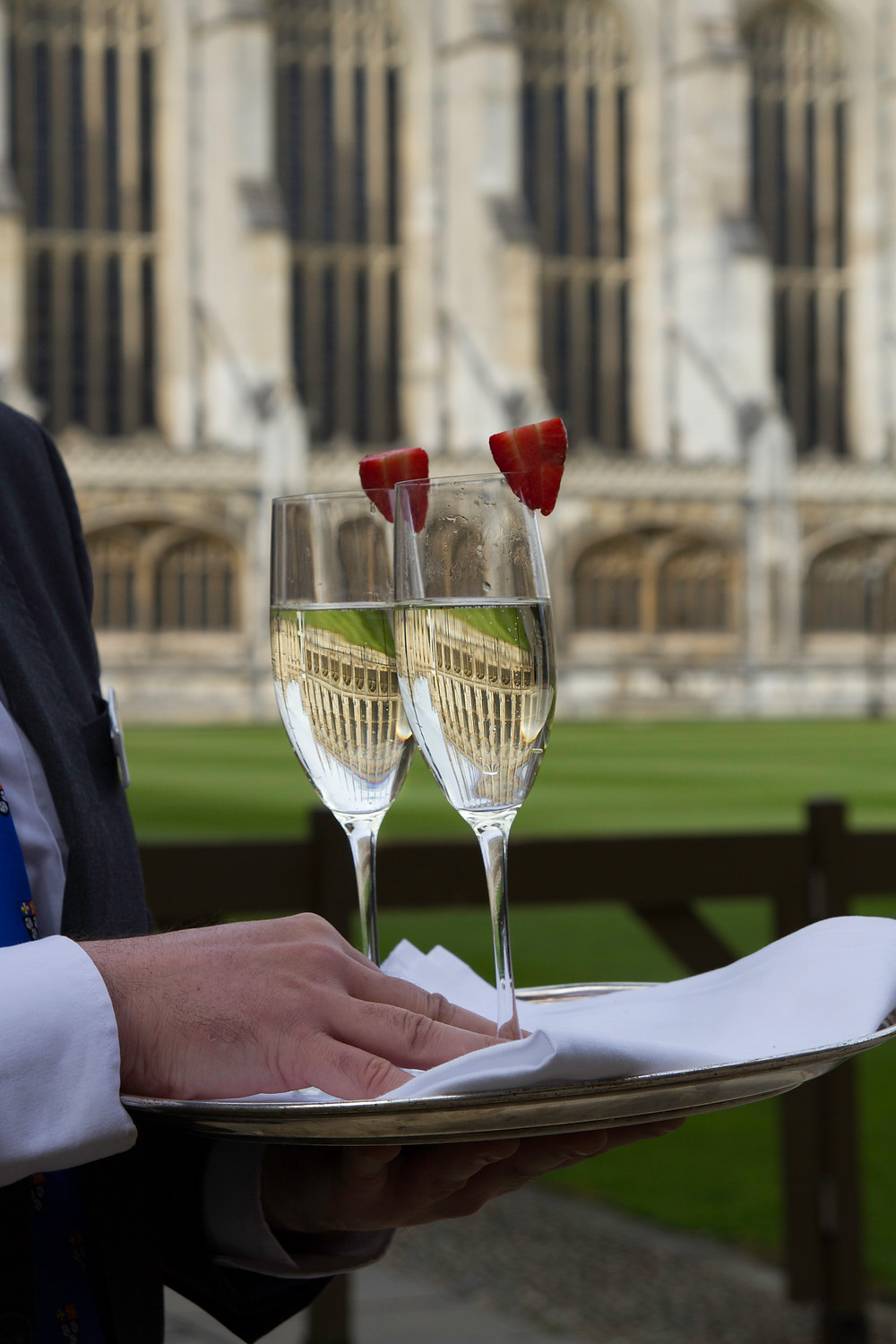 two champagne glasses with Kings college chapel reflected in the glasses - held by waiter who is only partially shown.