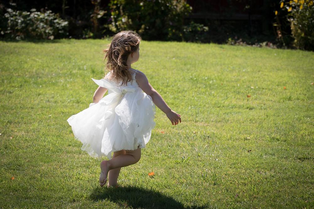 Girl in white dress running on grass