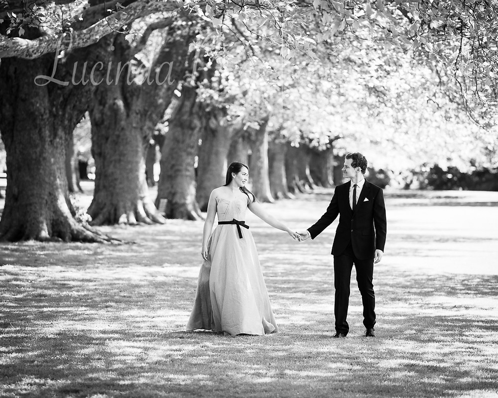 Couple in ball gown and suit outdoors under trees