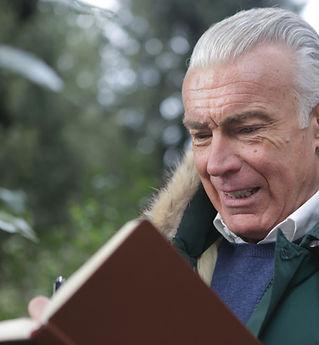 sad-elderly-man-writing-on-brown-noteboo