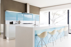 130609885-white-and-clean-modern-kitchen-with-stools-at-kitchen-island