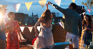 couple dancing at a rooftop dance party - man twirling woman as friends watch and smile