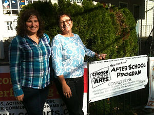 Co-creators Myrlin and Catherine stand next to a sign for an after school program