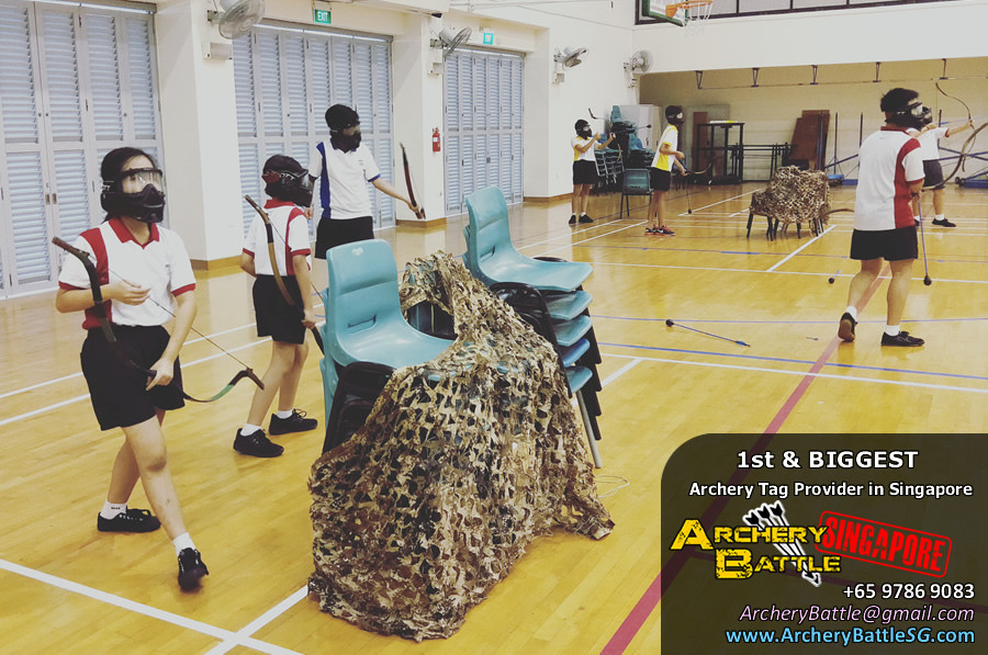 Students stack some chairs during an Archery Tag Singapore game