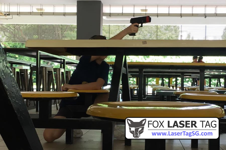Using canteen tables as cover in a Laser Tag Singapore game.