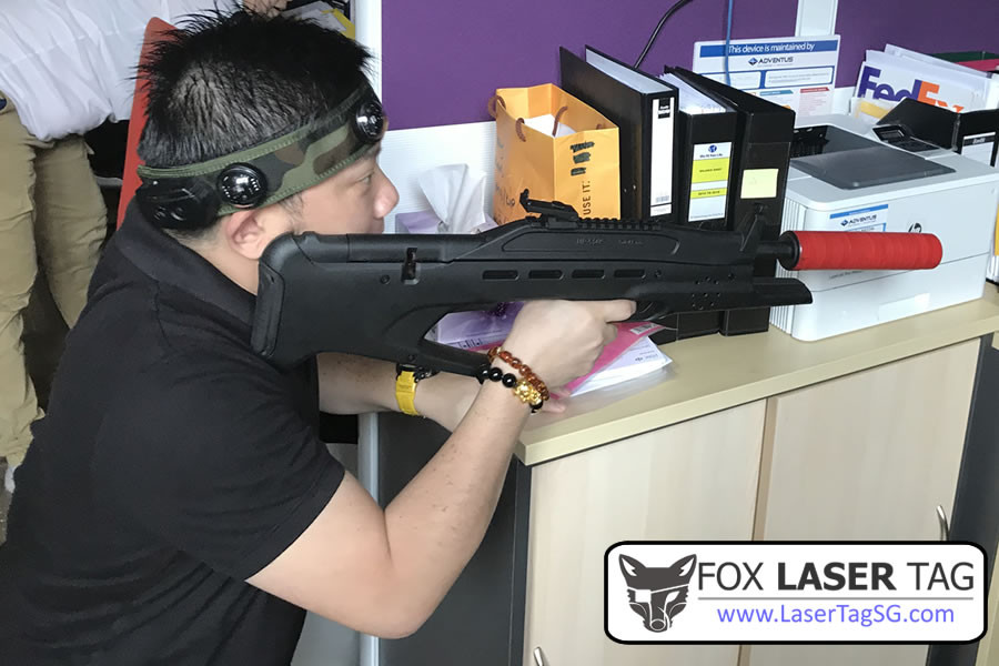 Laser Tag Singapore taking cover behind cabinet
