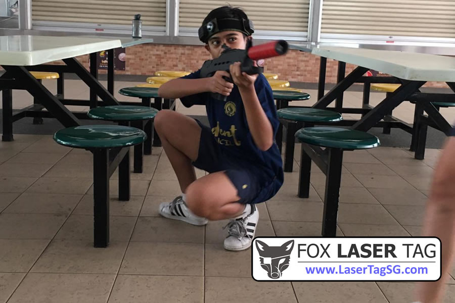 Sneaking and hiding around the tables in a Laser Tag Singapore game