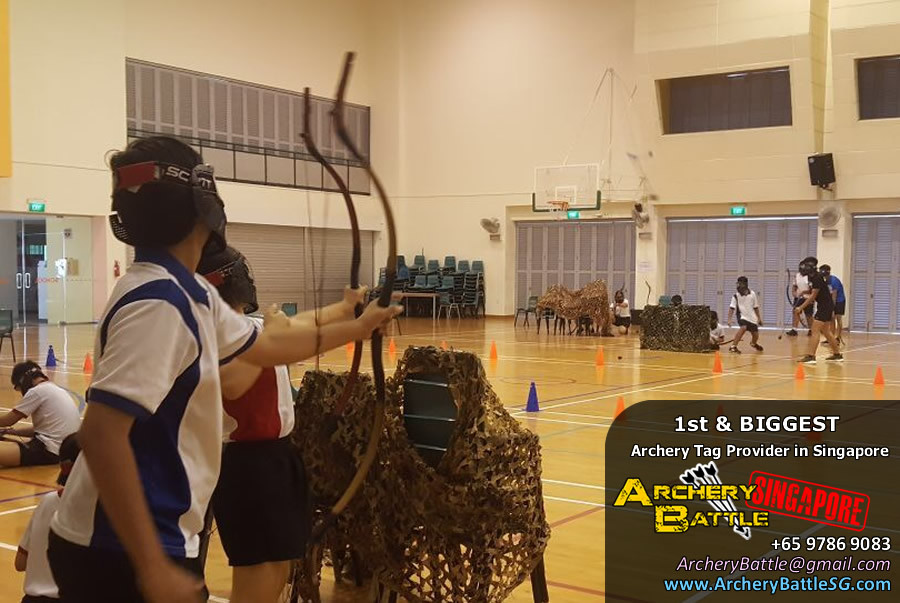 Students standing and shooting in an Archery Tag Singapore game