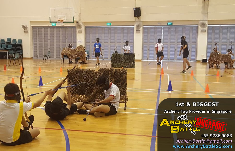Students hiding behind obstacles during Archery Tag Singapore game
