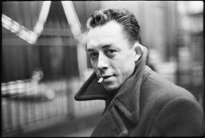 Albert Camus smoking in a coat