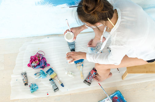 Young woman artist. She painting a sky o