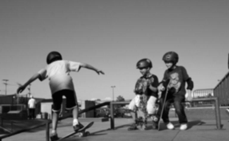 Young boys having fun learning to skateboard