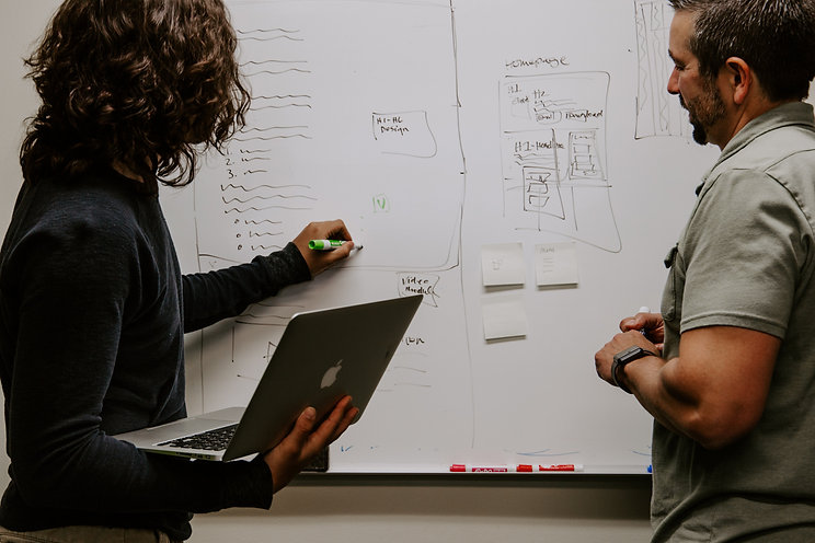 Two people are at a white board brainstorming ideas, with one person holding a macbook in their right hand and writing on the board with their other hand