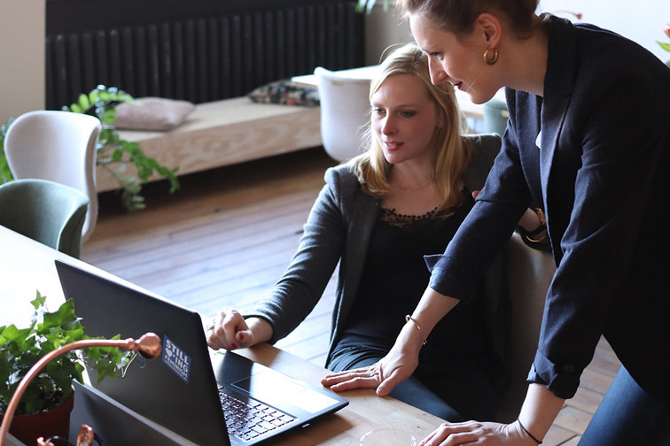 Two people are looking a laptop screen, one person is sitting down while the other peron is standing up and checking their work.