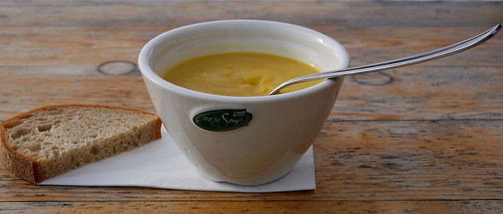A bowl of pumpkin soup and a small slice of bread with a napkin on a wooden table