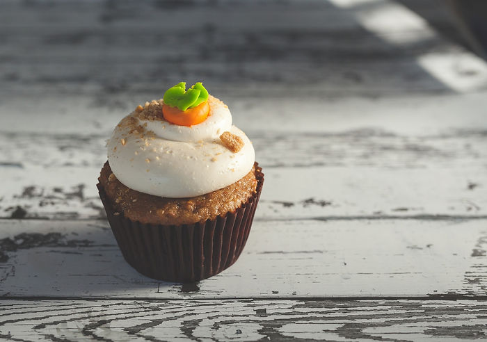 A photo of a carrotcake cupcake on a rustic white table with dim lighting