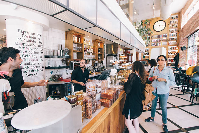 A busy cafe and two staff are engaged in cheeful conversation