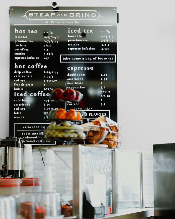 A photo of a cafe menu on the wall, as well as food on display of the cafe counter