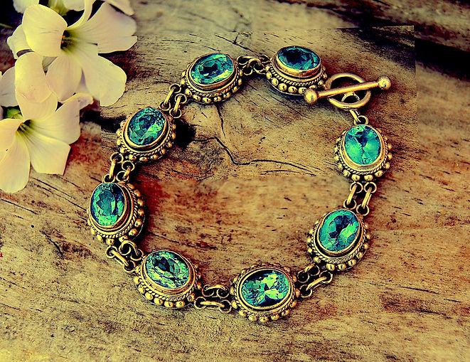A beautiful silver bracelet with turquoise gems next to some hibiscus flowers in a heavy yellow filter