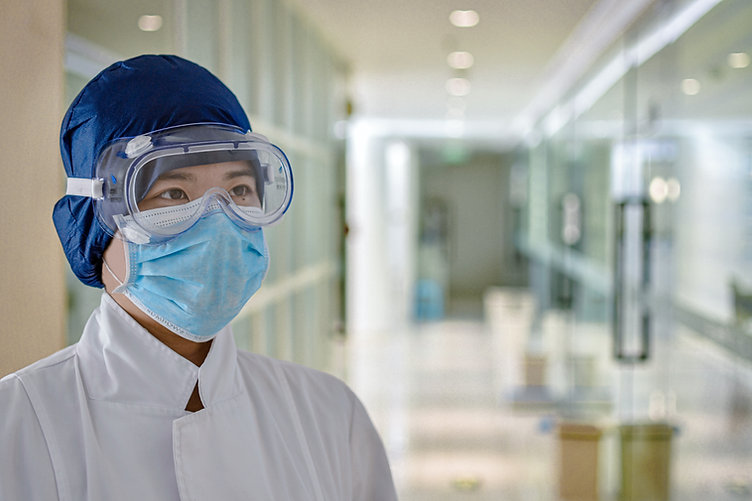A worker in a hospital is clothed in fully protected gear to keep safe