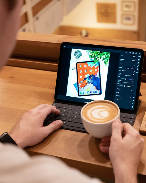 A person with coffee in their hand is re-sizing and retouching an image on a photo on an iPad