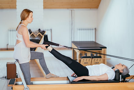 Instructor performing pilates with senio