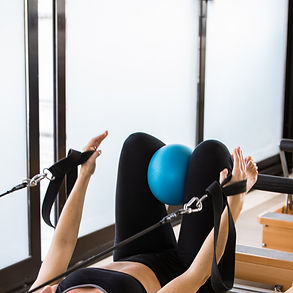 Woman exercising on pilates reformer  wi
