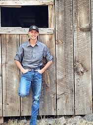 A picture of Alex Bafus standing in front of an Old barn wall.