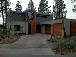 A modern style stucco house with double car garage accents in wood.