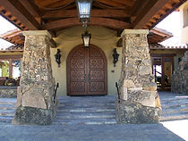 A Front entry Picture of a hotel with large stone columns an arched door and stucco walls.