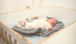 Baby liegt gemütlich im Wickelaufsatz mit hohen Umgrenzungen