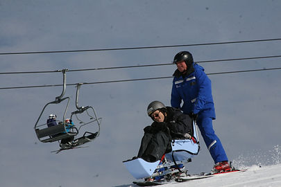 resident using adaptive sled going downhill skiing