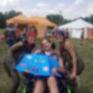 Staff with a client holding a sign at Warrior Dash