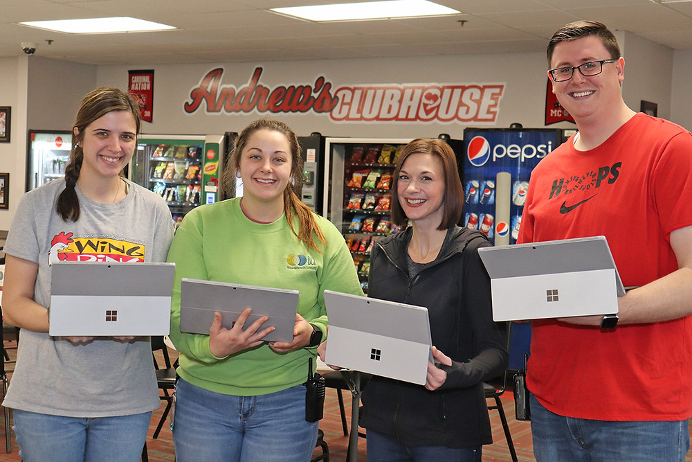 Four BCI staff hold tablets from EFC International