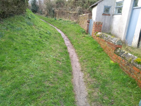 Overgrown inwards path by chapel