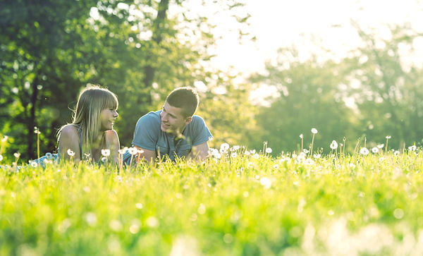 A white man and white woman lying in a field filled with pollen and flowers, smiling and conversing.