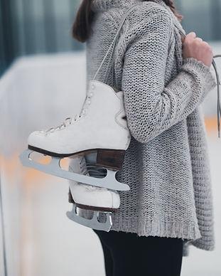 Woman at ice-skating rink holding skates..jpg