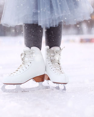 little girl is standing on ice in white figure skates.Winter active holiday concept..jpg