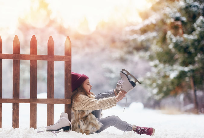 Happy child playing on a winter walk in nature. Cute little kid girl is going skate outdoo