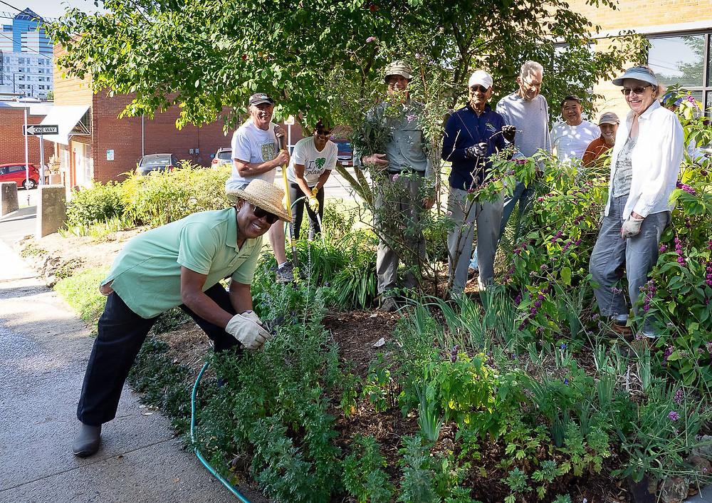 Master gardeners in demo garden, watering plants
