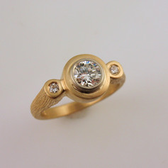 three bezel set diamond in a wood grained shank