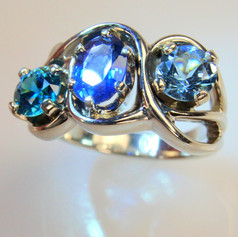 a lot of mothion in this modern flowing sapphire and blue diamond ring