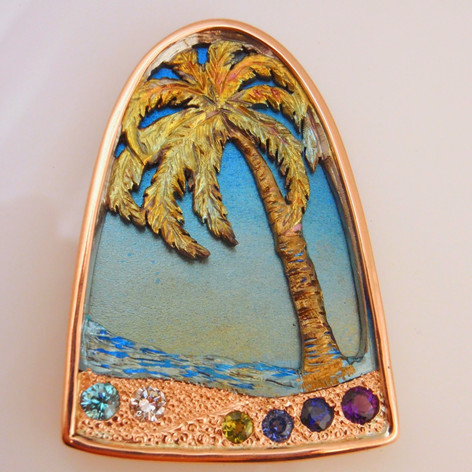 family pendant in yellow gold with colored titanium palm and ocean and sky backdrop.