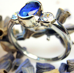 oval sapphire center w 1/2 bezel set diamond accents